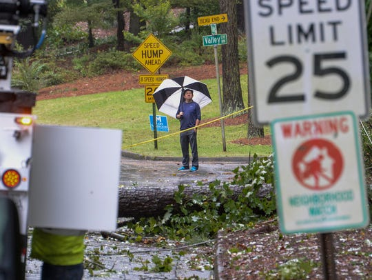 A man  looks at damage near her home on Tuesday, September