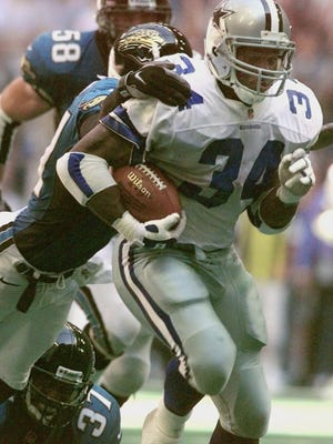 Herschel Walker, here with the Dallas Cowboys, had a 14-year career playing professional football. In this photo, Walker breaks free for a 64-yard touchdown pass on Oct. 19, 1997.