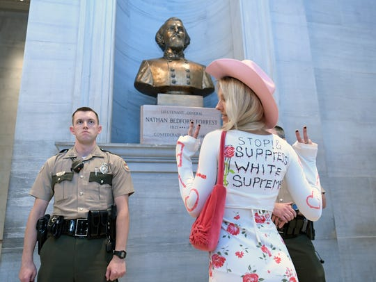 Sinclair Tucker of Knoxville poses for a friend in front of the bust of Nathan Bedford Forrest at the state Capitol on Aug. 14, 2017. About 75 activists condemning white supremacy gathered at the state Capitol in opposition to the bust housed there.