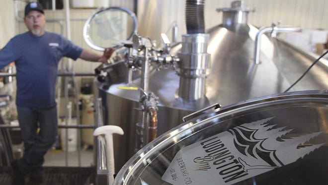 In a May 15, 2017 photo, Corey Wentworth, head brewer at Ludington Bay Brewing Company, explains some of the beer-brewing processes at the new facility located in Ludington, Mich.