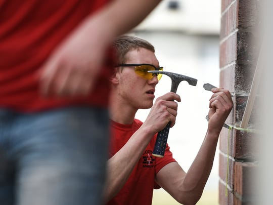 Matthew Brandt, a senior at Palmyra Area High School, works as students from the Lebanon County Career and Technology Center work on remodeling a building at the Lebanon County Fire School on Thursday, March 10, 2016.
