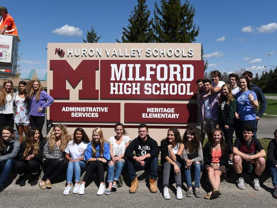 Students pose near the new sign at Milford High on