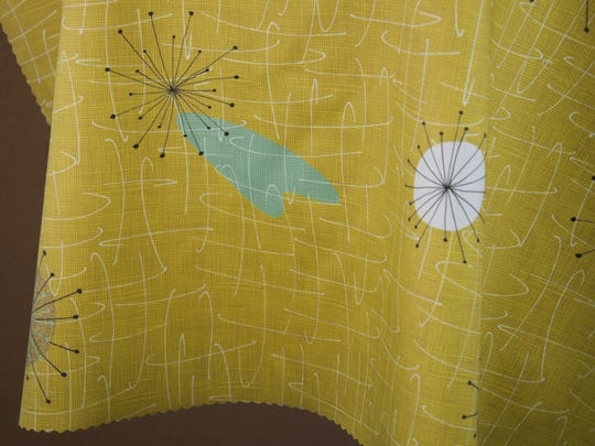 A detail of fabric design by Parisienne Christine Legeret who turns a fashion silhouette into an atomic age print she calls Midcentury Dress Cocktail, in a great mid-decade yellow with aqua accents. The prints come in an array of fabrics including cotton, silk crepe and even faux suede.