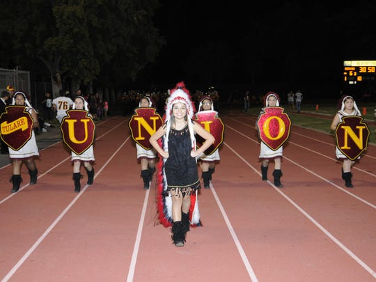 """The Tulare Union Color Guard walks on the track during a football game against Delano last season. Assembly Bill 30 would ban the use of """"Redskins"""" for the public schools."""