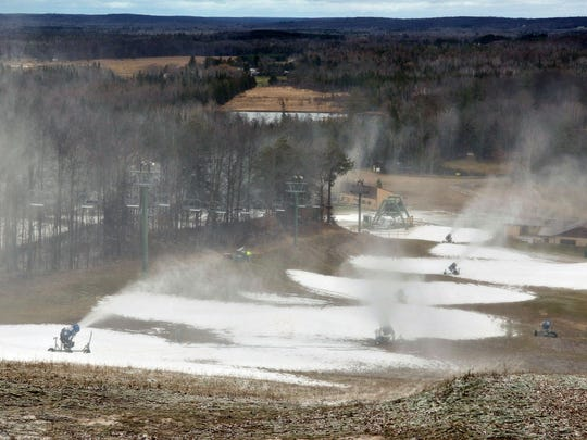 """Treetops Resort near Gaylord put snow machines to work the day after Thanksgiving, trying to provide snow for early season skiing. The lack of snow in Michigan has hurt sales of snowmobiles, skis and other winter sports equipment, kept ski slopes closed and delayed the formation of ice for skating and fishing. But Treetops has tried to make the best of the unseasonably warm weather. """"If you have a lift ticket, you can also play golf,"""" said Treetops' Kate Major."""