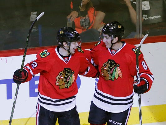 Chicago Blackhawks's Artemi Panarin, left, and Nick Schmaltz celebrate Schmaltz's goal during the second period of a preseason NHL hockey game against Detroit Red Wings Tuesday, Oct. 4, 2016, in Chicago. (AP Photo/Charles Rex Arbogast)