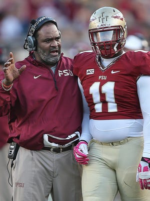 Veteran assistant coach Odell Haggins provides encouragement to Derrick Mitchell Jr. (11) during Florida State's 2013 season.