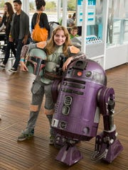 A girl in costume with a purple R2-D2 at Discovery World's Sci-Fi Day.