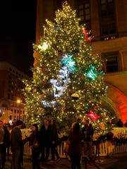 People attending the 103rd annual Christmas Tree lighting Thursday Nov. 17, 2016 stand around the tree to take photos after the official lighting.