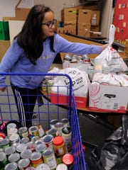 Ana Villalobos, 10, donates food to FoodLink for Tulare County's Stuff the Trolley campaign at Pinkham Elementary School.