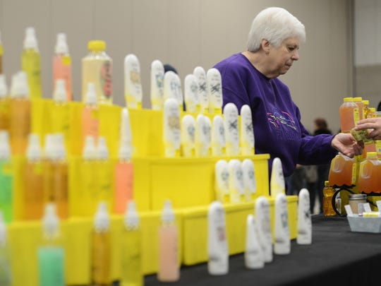 Rosie Jacobs exchanges money with a customer for Larry's Bee Natural products Saturday at the New Leaf Farmer's Market in the KI Convention Center.