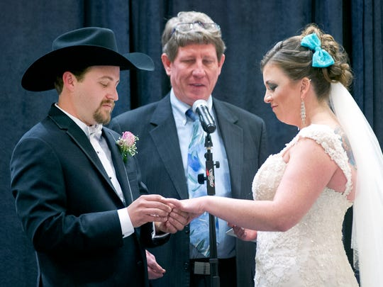 Garrett Arnold places the rings on Andrea Moore with Reverend Jess Williams officiating at the couples wedding Sunday afternoon at the Las Cruces Bridal Showcase.