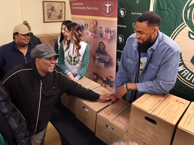Milwaukee Bucks forward Jabari Parker (right) greets