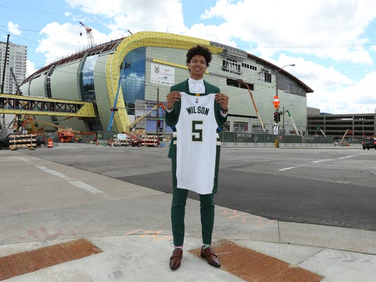 D.J. Wilson, the Milwaukee Bucks' first-round NBA draft choice, poses with his jersey outside the Bucks' new arena taking shape in downtown Milwaukee.