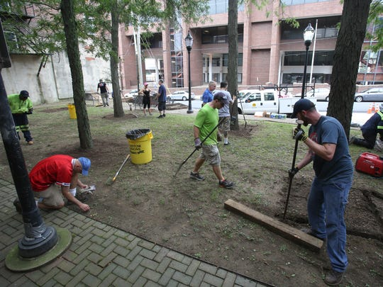 A couple of dozen volunteers and city workers make quick work of cleaning up Delaware Tech Plaza at Fourth and Shipley Streets in Wilmington on Saturday morning.