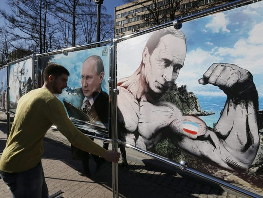 A man installs artwork of  Russian President Vladimir
