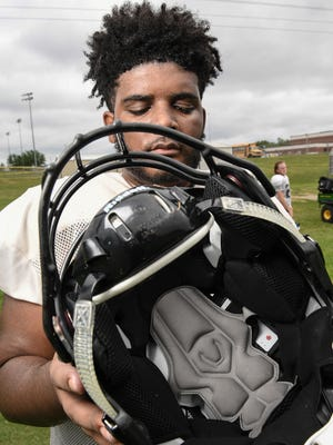Crescent High School offensive lineman Cam Richardson holds his football helmet with a sensor in it after practice in Iva on Monday. If the helmet on the player takes a hit, an alert is sent to a handheld receiver held by a trainer on the sidelines.