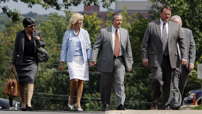 Mike Hubbard, center, walks to the Lee County Justice Center for a hearing holding hands with his wife Susan Hubbard, Monday, Aug. 17, 2015 in Opelika, Ala. Circuit Judge Jacob Walker tentatively pushed back Hubbard's ethics trial until a date in March that overlaps with the 2016 legislative session. Hubbard faces 23 felony ethics counts accusing him of using his public offices to enrich his businesses.