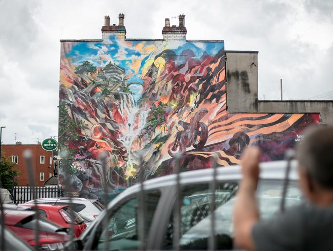 People stop to look a mural by artists Will Barras
