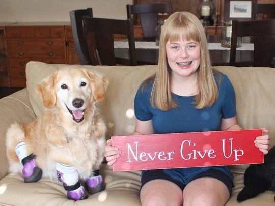 """""""Never give up"""" is the motto for the family of Chi Chi the golden retriever as she battles an aggressive form of cancer. Pictured is Chi Chi with Megan Howell."""