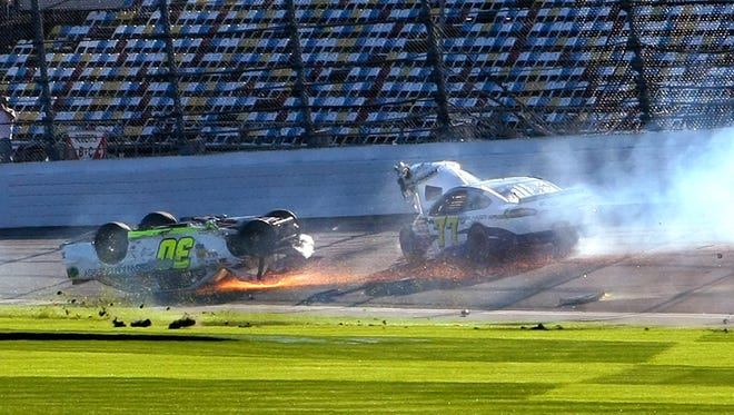 Parker Kligerman (30) slides upside down through the front stretch as Dave Blaney (77) goes around after a crash during a practice session for the NASCAR Daytona 500 auto race at Daytona International Speedway in Daytona Beach, Fla., Wednesday, Feb. 19, 2014. (AP Photo/Alex Menendez)