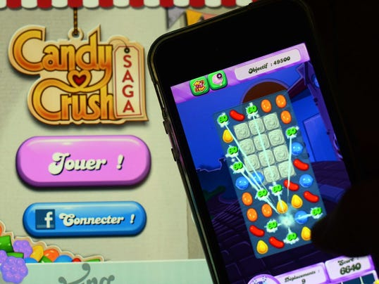In this file picture taken on January 25, 2014, a man plays Candy Crush Saga on his iPhone.
