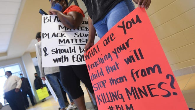 Leslie McCotry, left, and Britney Flemming stand with other protestors as they wait outside the Pender County Board of Education meeting at Topsail High School in Hampstead, N.C., Tuesday, June 16, 2020. The Pender County NAACP organized a protest after the school hired outside counsel over alleged racial slurs by school staff.