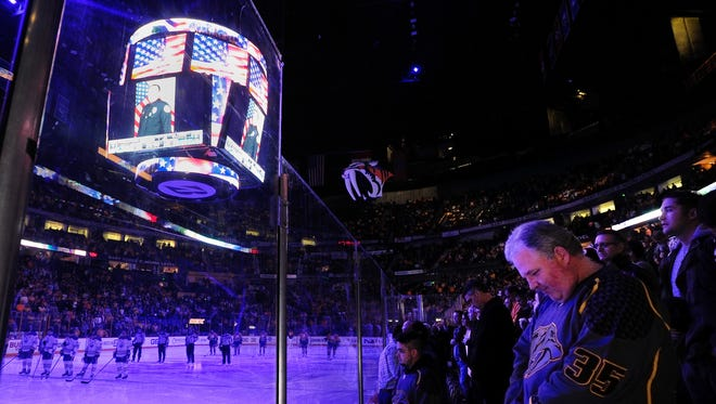 Fans observe a moment of silence to honor Metro Police Officer Eric Mumaw, who died trying to save a citizen who drove her car into the Cumberland River earlier in the day, before the Nashville Predators faced the Edmonton Oilers at Bridgestone Arena in Nashville, Tenn., Thursday, Feb. 2, 2017.