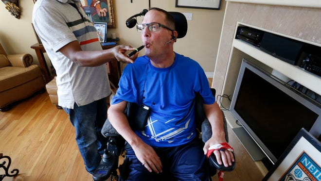 """In this Aug. 21, 2015 photo, multiple sclerosis patient and author of the memoir """"One day at a Time,"""" David Sloan, who is a medical marijuana patient, exhales smoke from medical cannabis concentrate given to him with help from his caregiver."""