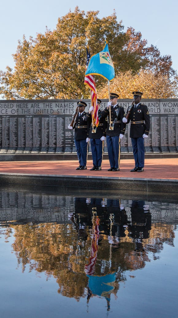 Members of the Delaware Army National Guard color guard stand at attention near the reflecting pool during the 2013 Veterans Day ceremony at the Delaware Memorial Bridge War Memorial in New Castle, Del.