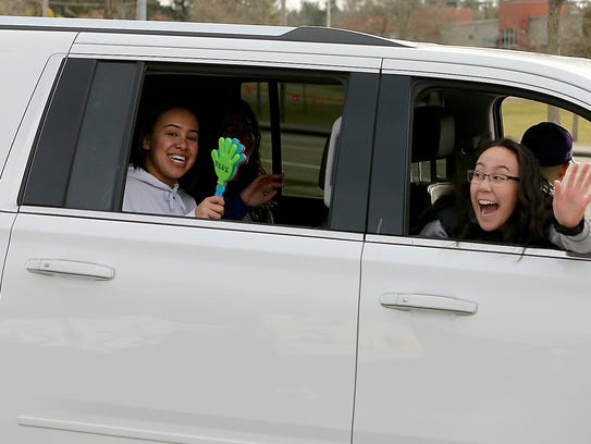 North Kitsap's Olivia Selembo shakes a noise maker from the back seat of an SUV as she and her Vikings teammates prepare to depart for the state tournament in Yakima on Tuesday.