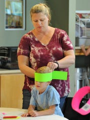 Susie Juhl measures her son, Skylar, 10, for an arts and crafts bugs hat during River Bend Nature Center's insects day.