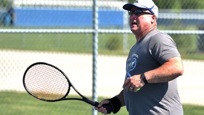 Centerville High School tennis Coach Randy Ecker works with players during practice Wednesday, April 26, 2017 in Centerville.
