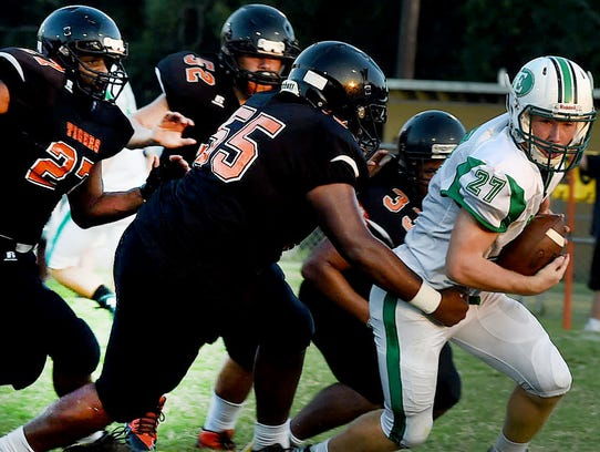 Eunice High's Avery Lee carries a host of Tiger defenders