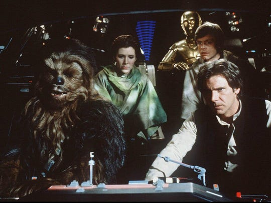 "Chewbacca, played by Peter Mayhew, left to right, Princess Leia, played by Carrie Fisher, C-3PO played by Anthony Daniels, Luke Skywalker, played by Mark Hamill, and Han Solo, played by Harrison Ford, appear in a scene from ""Star Wars: Return of the Jedi."""