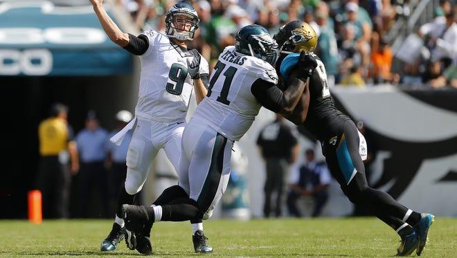 Eagles left tackle Jason Peters (center) blocks Jacksonville's Chris Clemons last Sunday.