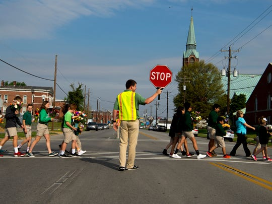 A procession of students cross Second Street during Holy Name School's Living Rosary service Wednesday morning.