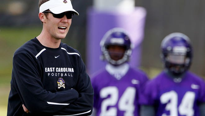 In this Wednesday, April 11, 2012 photo,  East Carolina offensive coordinator for quarterback Lincoln Riley coaches during football practice in Greenville, N.C. With Dominique Davis gone, East Carolina has an open race for its starting quarterback job. (AP Photo/Gerry Broome)