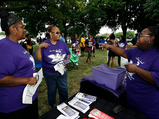Detroiters Pastor Angela Redmond, left, and Luviane Ward, center, speak to Tolice Lawrence, board member of Her Cries Are Heard, Preventing Crimes Against Females,  during a rally at Detroit's Roosevelt Park to unite and bring awareness to violence against females Saturday, Aug. 6, 2016.