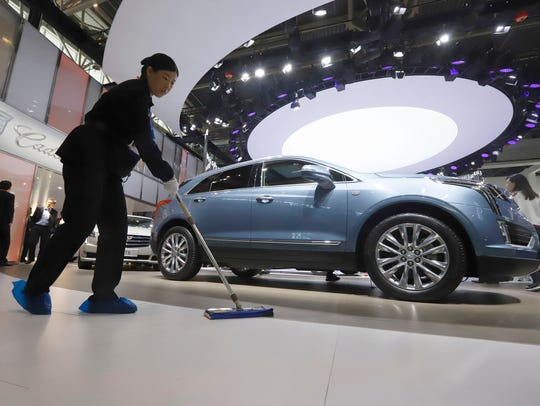 A worker cleans the floor near a Cadillac XT5 displayed
