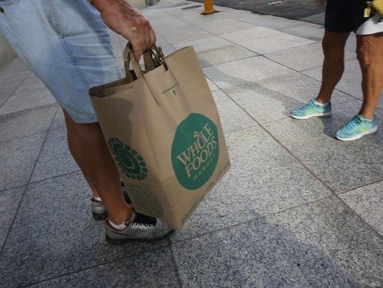 A customer carries his Whole Foods Market bag.
