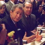 George W. Bush and Sen. Chuck Grassley enjoy conversation and coffee at the local sundries shop in Indianola on Jan. 20, 2000.