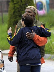 Family members of Grace Hughes hug each other in front of the burned home on Detroit's east side.