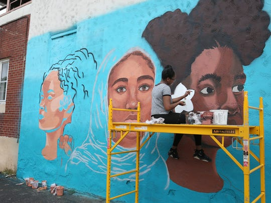 Kaori-Mei Stephens, 17, left, steps back to take in her progress as she works on her portrait while Etana Browne, 17, right, paints her arm to check on the skin tone colors as a trio of Rochester teen girls paint a large mural on the side of the Flying Squirrel at 285 Clarissa Street as part of Wall Therapy 2017.