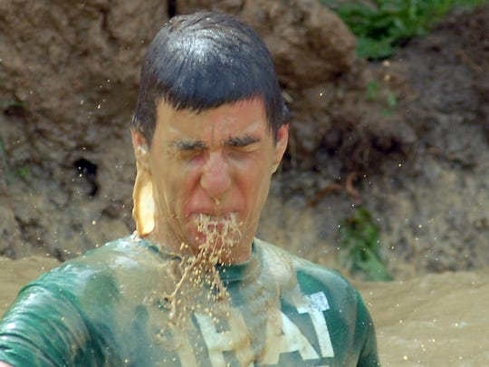 Muddy water runs from the face of Ryan Camastra, 18, of Port Huron after a fall into a large puddle during the Swampfoot 4 mile race.