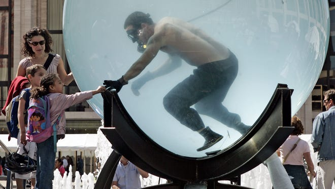 Stunt artist David Blaine, immersed in an 8-foot sphere filled with water, interacts with visitors observing his latest stunt, which is spending a week living in the sphere, in the plaza of New York's Lincoln Center, Monday May 1, 2006.