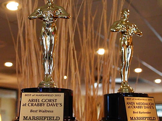 Ariel Gorst and Andy Meddaugh have Oscar-like statues for being chosen as the best waitress and best bartender by over over 500 participating entries in Marshfield Convention and Visitors Bureau Survey. Photo taken at Crabby Dave's restaurant in Marshfield.