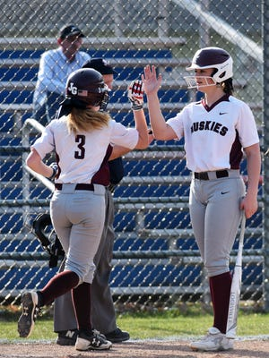 Paige German, left, is congratulated by Kaitlyn Zumbro after scoring a run in the in fifth inning during visiting John Glenn's 10-6 win against Maysville on Friday.