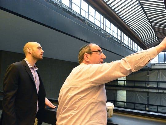Joel Shandelman (right) chief energy officer forBell Works, stands with Kyle Kirkpatrick, spokesman for Bell Works, as he points to new solar glass being  installed in Holmdel building.