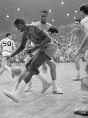 Courier & Press ArchivesSam Watkins, 12, (foreground) goes for a loose ball during the 1965 NCAA College Division Championship game at Roberts Stadium. UE won over Southern Illinois 85-82. Helping on the play for UE are Herb Williams (center) and Jerry Sloan, 52, (right).